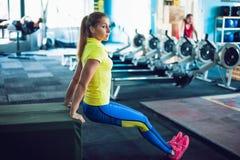 健身俱乐部的女孩 做蹲坐的年轻女运动员使用在健身房的长凳 库存图片