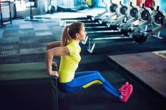 健身俱乐部的女孩 做蹲坐的年轻女运动员使用在健身房的长凳 免版税图库摄影