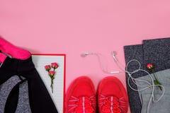 健身健康活跃生活方式体育鞋面视图运动鞋耳机给背景花淡粉红色穿衣 库存照片