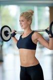 健身健身房举的重量的少妇 库存图片