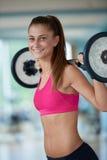 健身健身房举的重量的少妇 免版税库存照片
