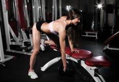 健身健身房妇女力量训练举的哑铃重量 图库摄影