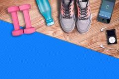 健身健身房席子和浅粉红色的哑铃 适合的设备鞋子和音乐播放器 库存图片