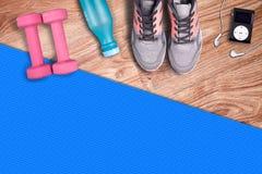 健身健身房席子和浅粉红色的哑铃 适合的设备鞋子和音乐播放器 免版税图库摄影