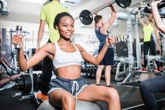 健身健身房的女孩行使她的在机器的肩膀 免版税库存图片