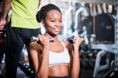 健身健身房的女孩行使她的肩膀的 库存照片