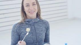 健身和健康食物 妇女是休息和吃健康食品在白色的一种锻炼以后  股票视频