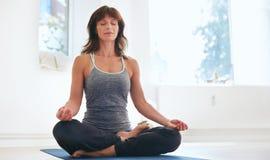 健身在健身房的女性实践的Padmasana 库存图片
