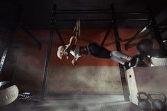 健身在TRX的妇女锻炼在健身房 免版税库存照片
