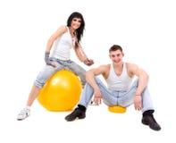 年轻健身夫妇佩带的牛仔裤在演播室 免版税库存照片