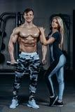 健身夫妇-妇女和人有哑铃的在健身房 免版税库存图片