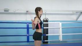 健身女孩做与跳绳的心脏锻炼在复杂的体育的圆环 股票录像