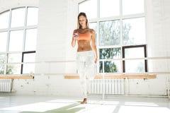 健身女孩训练在应用的白色健身房和计数卡路里在手机 图库摄影