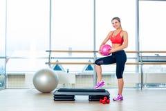 健身女孩,佩带在运动鞋,红顶和黑后膛,摆在有球的步委员会,运动器材 免版税库存图片