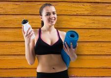 健身妇女、水和瑜伽席子有黄色木背景 库存照片