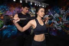 健身妇女举的重量、体育、体型、生活方式和人概念-年轻人和妇女有屈曲肌肉的杠铃的 免版税图库摄影