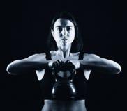 健身妇女举的水壶响铃 免版税库存照片