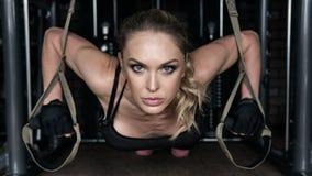 健身妇女在健身房进行在停止圈的俯卧撑 免版税库存照片