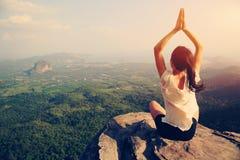 健身妇女在山峰峭壁的实践瑜伽 图库摄影