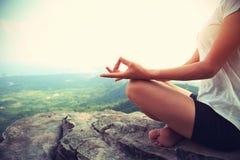 健身妇女在山峰峭壁的实践瑜伽 免版税库存图片