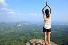 健身妇女在山峰峭壁的实践瑜伽 库存照片