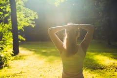 年轻健身妇女在早晨森林里 免版税库存照片