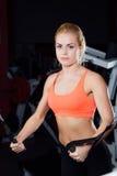 年轻健身妇女展示天桥锻炼 胸肌,与锻炼机器缆绳的坚硬训练 免版税库存照片