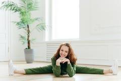 健身妇女展示好的灵活性,做体操锻炼,显示腿分裂,保留手在下巴下,广泛地微笑, 免版税库存照片