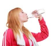 健身妇女有毛巾饮用水的体育女孩从被隔绝的瓶 免版税库存照片