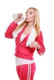 健身妇女有毛巾饮用水的体育女孩 免版税库存图片