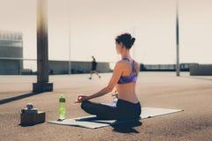 健身妇女概念 瑜伽和凝思在一个现代urbanistic城市 年轻可爱的女孩-瑜伽思考反对 免版税库存照片