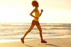 健身妇女由海负责在黄昏 图库摄影