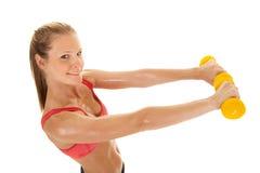 健身妇女红色体育胸罩举行两个称重 免版税图库摄影