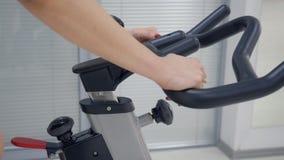 健身妇女藏品把手室内自行车的手调整一会儿训练的 股票视频