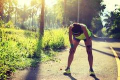 健身妇女赛跑者休假在早晨热带森林足迹 库存图片