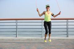 健身妇女跳绳在海边 免版税库存照片