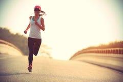 健身妇女运行在城市道路的足迹赛跑者 免版税图库摄影