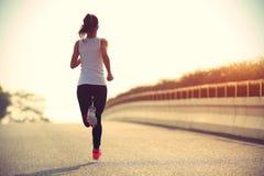 健身妇女运行在城市道路的足迹赛跑者 库存图片