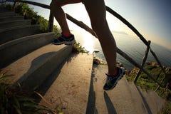 健身妇女运行在海边山台阶的赛跑者腿 免版税库存照片
