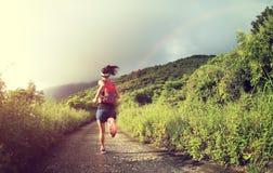 健身妇女运行在海边山的足迹赛跑者 库存图片