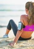健身少妇坐海滩。背面图 图库摄影