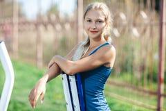 健身少妇画象一件蓝色衬衣的使用室外健身房设备在看照相机和微笑的公园 库存照片