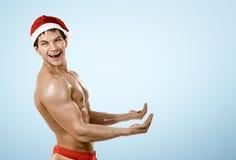 健身性感的圣诞老人举行和微笑,在蓝色背景 免版税库存照片