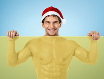 健身性感的圣诞老人,与黄色横幅和微笑的立场 免版税库存图片