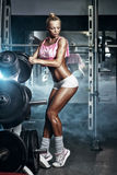 健身性感的白肤金发的女孩设置在杠铃的重量在健身房 库存图片