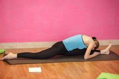 健身或瑜伽类,做锻炼的妇女教练员  免版税库存图片