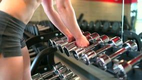 健身房举的重量的肌肉运动员妇女 健身女孩采取哑铃 体育,秀丽,健身的概念 影视素材