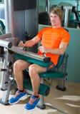 健身房安装了腿卷毛机器锻炼白肤金发的人 免版税库存照片