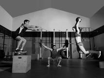 健身房小组锻炼杠铃关上球并且跳跃 免版税库存照片