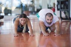 健身房男人和妇女俯卧撑与哑铃的力量pushup在健身锻炼 免版税库存照片